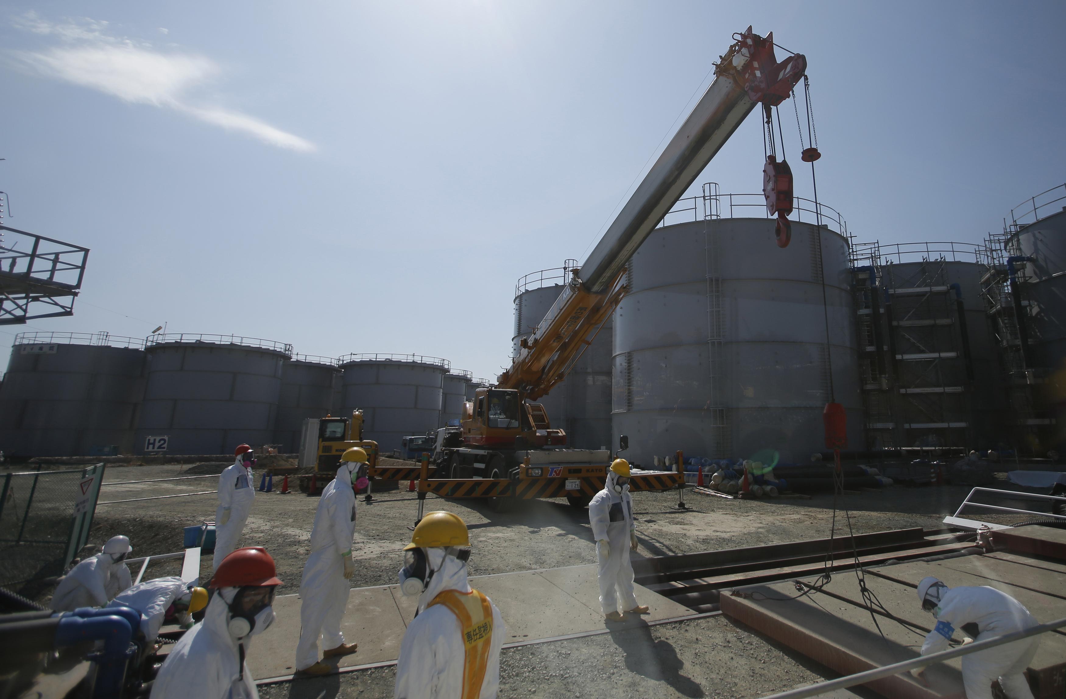 Des travailleurs prêts d'un réservoir d'eau de la centrale de Fukushima au Japon © AFP PHOTO / POOL / Issei KATO