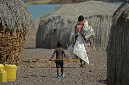 A mother and child walk in the village of Komote on the shores of Lake Turkana, northern Kenya on May 18, 2012. The Kenyan government and UNESCO on Wednesday announced the discovery of a huge supply of underground water in the impoverished, drought-stricken extreme north of the country. © AFP/File Carl de Souza