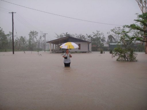 Photo taken on March 8, 2011 shows a woman standing in floodwater during heavy rain in Cardwell, Australia. Climate change caused by human use of fossil fuels played a role in about a half dozen extreme weather events last year, international scientists said Thursday. © AFP/File Lindsay Hallam