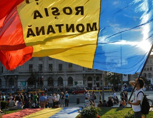 A protester holds a Romanian flag reading