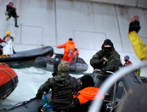 A handout photo taken by Greenpeace on September 18, 2013, shows an officer of the Russian Coast Guard pointing a gun at a Greenpeace International activist during environmentalists' attempt to climb an Arctic oil platform in the Pechora Sea. © GREENPEACE/AFP Denis Sinyakov