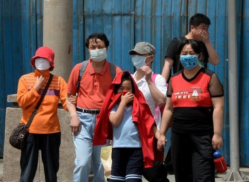 People wear masks to protect against air pollution and dust in Beijing on May 19, 2013. © AFP/File Mark Ralston