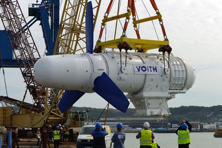 FRANCE, Cherbourg-Octeville : A crane carries the first HyTide underwater turbine built by German company Voith Hydro at Cherbourg's shipyard (CMN), to put it in the water, at Cherbourg's port, on June 14, 2013. The exercise's goal was to test the handling device. The turbine was put into the water for ten minutes and then put on a barge to be shipped to Scotland. AFP PHOTO / JEAN-PAUL BARBIER