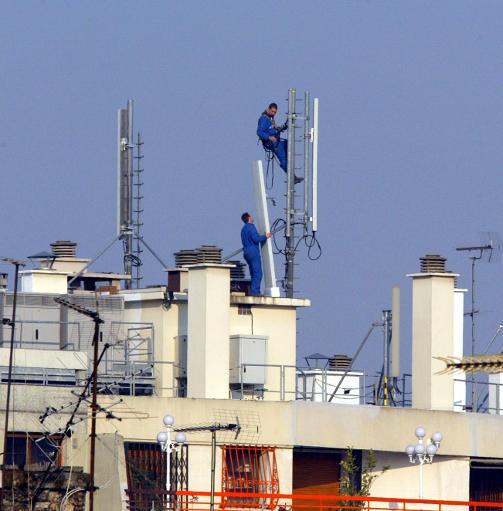 Des techniciens installent des relais téléphoniques sur le toit d'un immeuble parisien, en 2003 © AFP/Archives Jacques Demarthon
