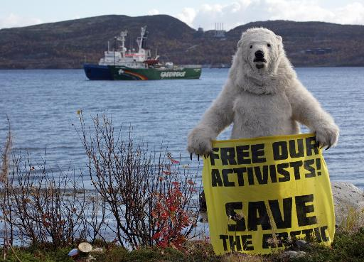 A Greenpeace activist dressed as a polar bear holds a banner in front of the Arctic Sunrise protest ship in Kola Bay, Murmansk, on September 24, 2013 © Greenpeace International/AFP/File Igor Podgorny