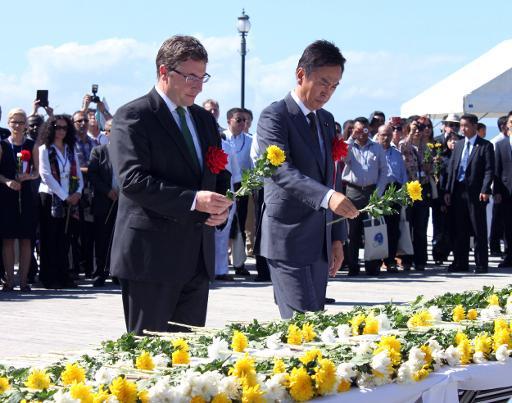 Le ministre japonais de l'Environnement Nobuteru Ishihara (d) et le directeur du PNUE, Achim Steiner, rendent hommage aux victimes de Minamata, le 9 octobre 2013 © JijiPress/AFP JijiPress