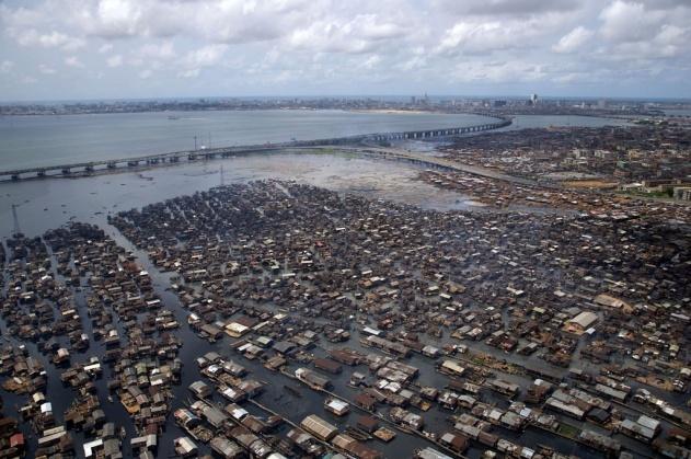 Bidonville de Makoko, lagune de Lagos, État de Lagos, Nigéria (6°0' N - 3°24' E). © Yann Arthus-Bertrand/Altitude Située au bord de l'océan Atlantique et d'une lagune, Lagos est la plus grande ville du Nigéria et le principal centre commercial et industriel, mais ne possède aucun attrait touristique. Ancienne capitale du pays, l'agglomération souffre d'un accroissement démographique démesuré depuis son indépendance en 1960 et compte aujourd'hui 9 millions d'habitants. Un pont de 10 kilomètres, le Third Mainland Bridge, qui relie les quartiers d'affaires du centre-ville situés sur l'île de Lagos à l'aéroport surplombe Makoko, un bidonville sur la lagune. Des pêcheurs, venus chercher fortune depuis la frontière du Bénin, s'y sont entassés dans des cabanes sur pilotis où l'on ne peut se rendre qu'en pirogue. A Makoko où vivent plus de 100 000 personnes, il n'y a ni eau courante, ni électricité, ni assainissement. Premier pays africain producteur de pétrole par le volume de sa production avec 2,6 millions de barils/jour en 2010, le Nigéria demeure relativement pauvre. Ce pays qui est le plus peuplé d'Afrique avec 155 millions d'habitants a officiellement (en réalité sans doute beaucoup moins) une capacité de production d'électricité de 5 900 MW pour l'ensemble de son territoire : face aux coupures incessantes, usines, entreprises et hôpitaux doivent le plus souvent recourir à de coûteux et polluants générateurs diesel.