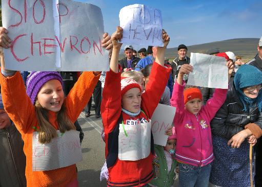 Des enfants tiennent des affichettes pour protester contre la décision du géant américain Chevron de commencer des travaux d'exploration pour les gaz de schiste dans leur commune, le 15 octobre 2013 à Pungesti (200km au nord-est de Bucarest) © AFP Adrian Arnautu