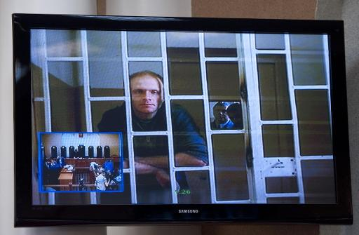 Greenpeace International contracted freelance photographer Denis Sinyakov from Russia is seen on a TV screen during his bail hearing at a court in Murmansk, northern Russia on October 8, 2013 © Greenpeace/AFP Dmitri Sharomov