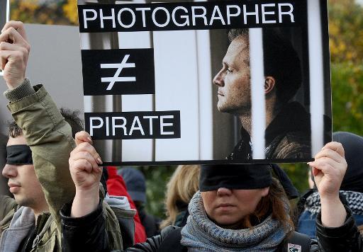 Des dizaines de journalistes russes ont manifesté dimanche à Saint-Pétersbourg pour exiger la libération du photographe Denis Siniakov, arrêté fin septembre avec des militants de Greenpeace pour une action contre une plateforme pétrolière en Arctique, et accusé de piraterie. © AFP Olga Maltseva