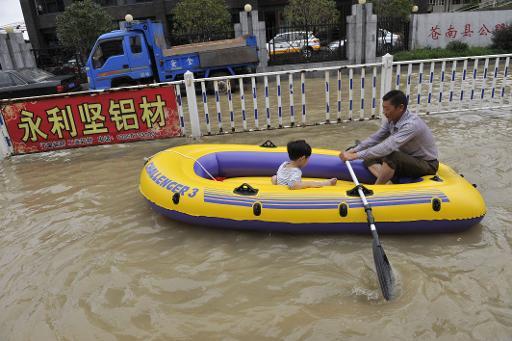 Residents make their way through a flooded street on an inflatable boat in disaster-hit Cangnan county of Wenzhou, east China's Zhejiang province, on October 7, 2013 © AFP