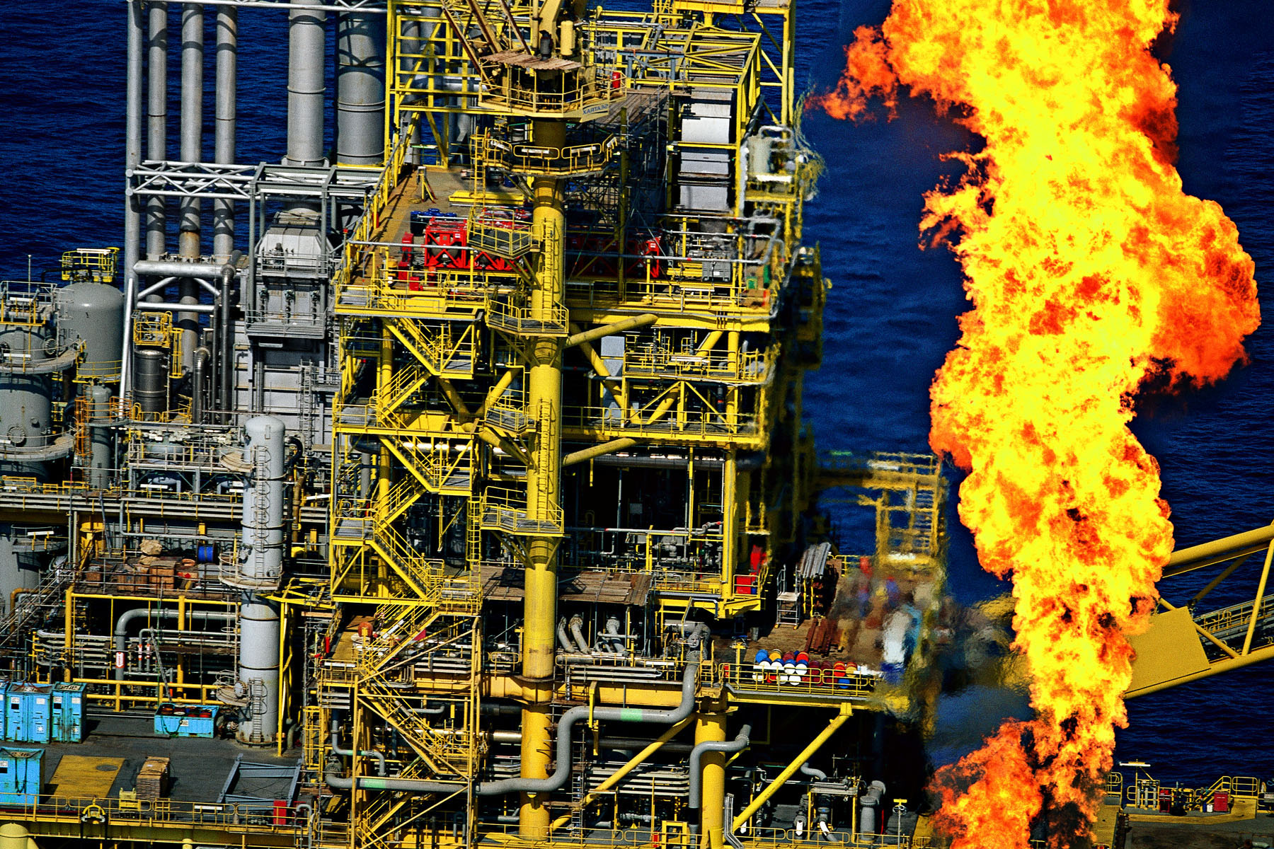 Plateforme pétrolière Al-Shaheen Ad, Qatar (25° 30' N - 51° 30' E). Le torchage consiste à bruler les gaz naturels d'un gisement de pétrole, car leur exploitation n'est pas rentable. Chaque année, les torchère sont responsables du gaspillage de 150 milliards de m3 de gaz, ce qui équivaut à 390 millions de tonnes de gaz à effet de serre, ou encore à 2% du total mondial des émissions de gaz à effet de serre émis. © Yann Arthus Bertrand/Altitude.