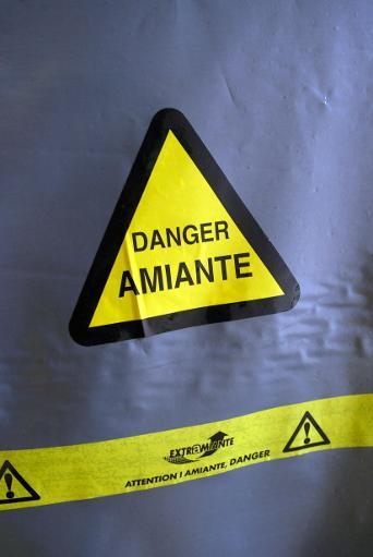 Une bâche portant un symbole de danger couvre, le 2 juillet 2002 à Paris, un endroit d'un bâtiment où de l'amiante a été utilisé pour l'isolation © AFP/Archives Jean-Pierre Muller