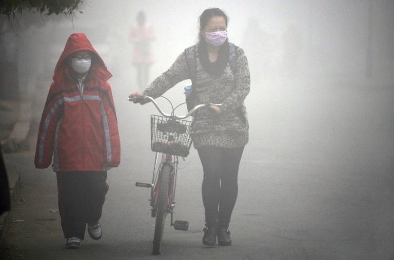 Jilin, Chine : une femme et son enfants marchent dans les rues de Jilin lors d'un épisode de smog au nord est de la Chine en octobre 2013. © CHINA OUT AFP PHOTO