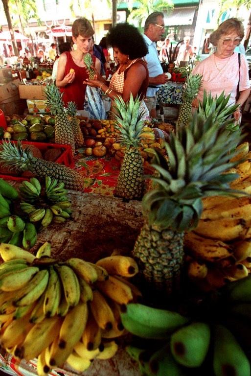 FRANCE, POINTE-A-PITRE : marchande de fruits installée sur le marché de Pointe-à-Pitre en Guadeloupe. L'UICN et le MNHN viennent de publier le premier volet de la Liste rouge des espèces de la flore menacée en Guadeloupe et Martinique. © AFP