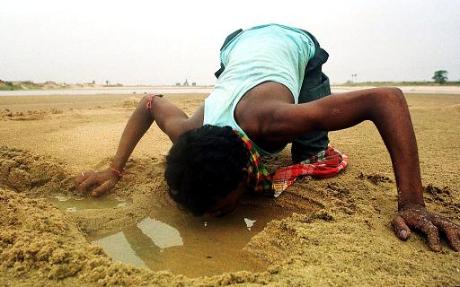 A labourer quenches his thirst from a water-hole dug at a dried-up river bed at Birbhum in the eastern Indian state of West Bengal on May 22, 2000 © AFP/File Dibyangshu Sarkar