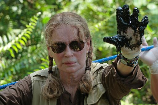 US actress Mia Farrow shows her left hand soiled with oil during a visit to an area in the Amazon affected by pollution created by US oil company Chevron, in Lago Agrio, Aguarico, Ecuador, on January 28, 2014 © AFP Juan Cevallos