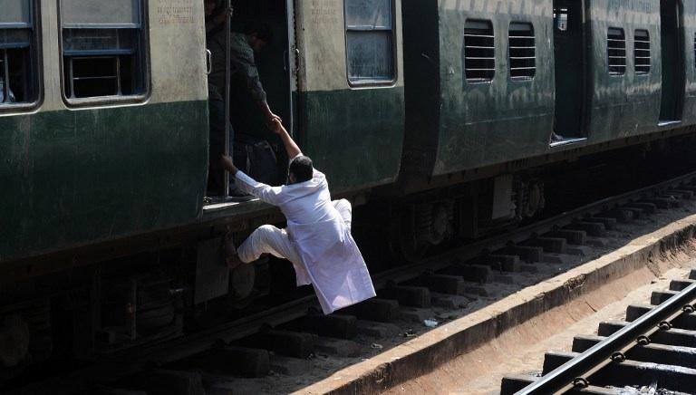 Inde, Calcutta: un passager indien grimpe à bord d'un train en marche. © AFP PHOTO/ DIBYANGSHU SARKAR