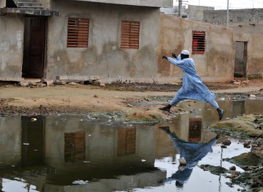 A man jumps over a pond of stagnant water in the suburbs of Dakar on October 9, 2008 © AFP/File Georges Gobet