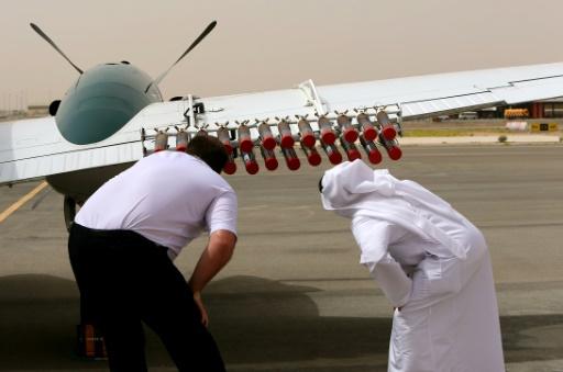 Un pilote et un fonctionnaire des Emirats arabes unis vérifient sur un avion Beechcraft les fusées destinées à injecter des cristaux de sels dans les nuages pour tenter de provoquer de la pluie, le 23 avril 2015 à l'aéroport d'Al-Aïn © AFP MARWAN NAAMANI