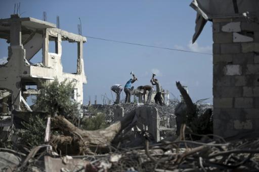Des travailleurs dégagent les ruines d'un bâtiment détruit pendant la guerre de 50 jours entre Israël et le Hamas en 2014, le 25 août 2015 à Gaza © AFP MOHAMMED ABED