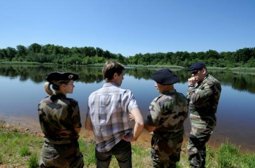 Un membre du Conservatoire des espaces naturels parle avec des militaires près d'un lac appartenant au camp militaire de Chambaran, près de Viriville, en Isère, le 11 juin 2014 © AFP/Archives Jean-Pierre Clatot
