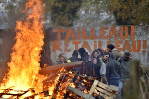 Des activistes de la Zad derrière une barricade érigée pour bloquer l'accès à la ferme Bellevue à Notre-Dame-des-Landes le 2 décembre 2016 © AFP LOIC VENANCE