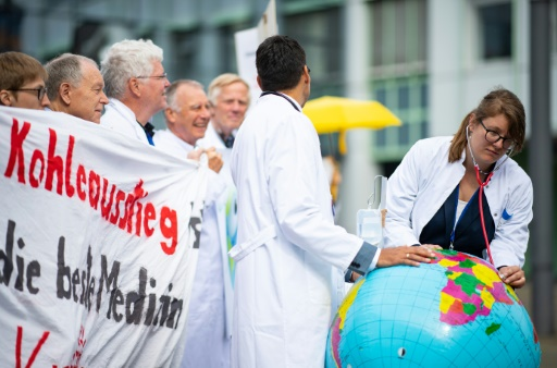 """Deux médecins de l'organisation """"Doctors For Future"""" ausculent une Terre en baudruche lors d'une manifestation pour la protection du climat en marge d'un congrès de médecins à Munster (nord-ouest de l'Allemagne), le 28 mai 2019 © dpa/AFP Guido Kirchner"""