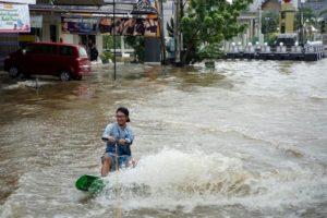 Photo récupérée par l'AFP auprès du compte Instagram de Muhammad Fahri Ramadhan, le montrant en train de s'exercer au wakeboard dans une rue inondée de Samarinda, sur l'île indonésienne de Borneo, le 16 juin 2019 © Muhammad Fahri Ramadhan/AFP Handout