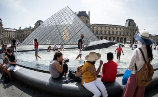 Des touristes se rafraîchissent au bord d'une fontaine de la pyramide du Louvre à Paris pendant une vague de chaleur, le 7 août 2018 © AFP/Archives GERARD JULIEN