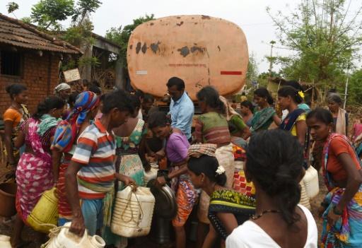Des villageois remplissent des bidons d'eau livrée par camion citerne, dans le village indien de Shakar Pada, le 10 juin 2019 © AFP PUNIT PARANJPE