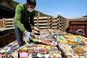 Un employé de la décharge de Kamikatsu empile des cannettes compactées, le 14 mars 2019 au Japon © AFP Kazuhiro NOGI