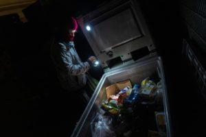 """Un """"cambrioleur de poubelles"""" inspecte celle d'un supermarché pour lutter contre le gaspillage alimentaire, le 17 mai 2019 à Berlin © AFP John MACDOUGALL"""