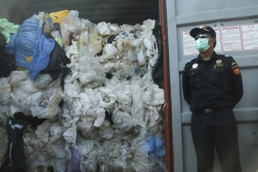 Un policier indonésien devant un conteneur rempli de déchets illégalement importé vers le pays, à Batam le 29 juillet 2019 © AFP SEI RATIFA