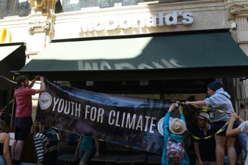 Des militants du mouvement les jeunes pour le climat affichent une banderole devant un restaurant McDonald's à Bordeaux le 14 juillet 2019 © AFP MEHDI FEDOUACH