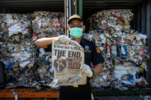 Un douanier indonésien montre un journal tiré d'un conteneur rempli de déchets non conformes qui vont être renvoyés en Australie, à Surabaya le 9 juillet 2019 © AFP Juni Kriswanto