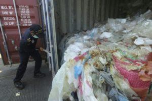 Un policier indonésien ouvre un conteneur rempli de déchets illégalement importé vers le pays, à Batam le 29 juillet 2019 © AFP SEI RATIFA
