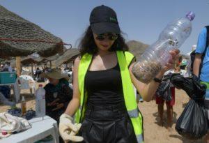 Une volontaire de l'association Tounes Clean-Up, qui organise des opérations de nettoyage toute l'année, ramasse des mégots de cigarettes sur la plage de La Marsa, près de Tunis, le 14 juillet 2019 © AFP FETHI BELAID