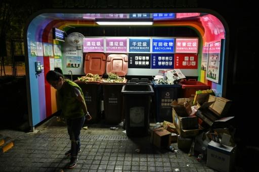 Une femme passe devant un espace de tri des déchets dans un quartier résidentiel de Shanghai le 11 juillet 2019. © AFP HECTOR RETAMAL