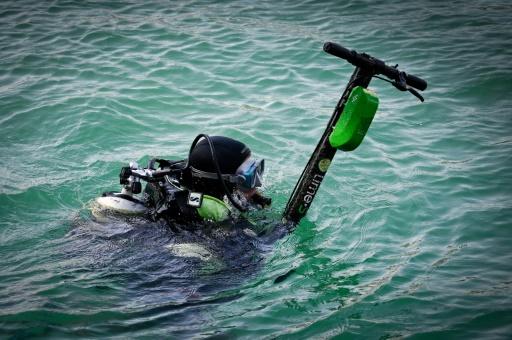 Un plongeur volontaire remonte une trottinette jetée à l'eau à Marseille le 20 juillet 2019 © AFP GERARD JULIEN
