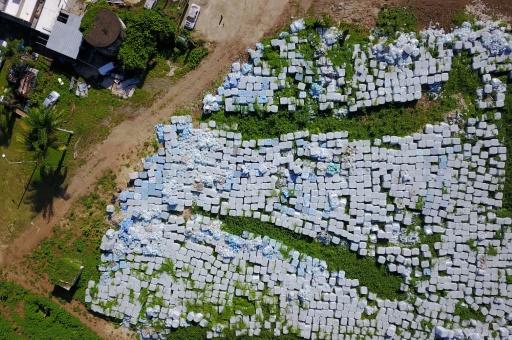 Des dizaines de milliers de bouteilles d'eau destinées à l'aide d'urgence dans un champ de la localité de Dorado, à 40 km de Porto Rico, San Juan, le 28 juillet 2019 © AFP Ricardo ARDUENGO