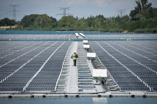 Un technicien marche entre les panneaux photovoltaïque de la centrale flottante O'Megal, le 30 juillet 2019 à Piolenc, dans le Vaucluse © AFP GERARD JULIEN
