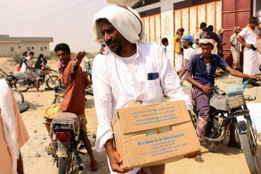 Des Yéménites originaires portent des cartons fournis par le Programme alimentaire mondial, le 8 juillet 2019 dans le secteur d'Abs, au nord-ouest du pays © AFP/Archives ESSA AHMED