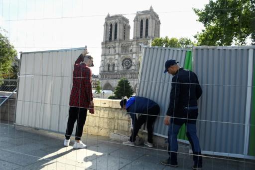 Des ouvriers installent des palissades le 13 août 2019, près de Notre-Dame de Paris en vue de la décontamination des rues alentour de la cathédrale © AFP BERTRAND GUAY