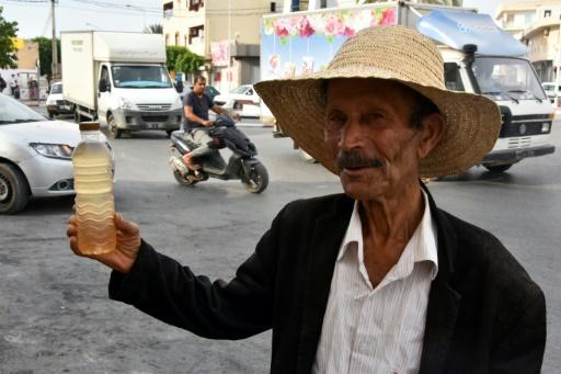 Un homme vend une bouteille de legmi, de la sève de dattier, dans une rue de Gabès, dans le sud de la Tunisie, le 18 juillet 2019. © AFP Mourad MJAIED