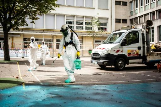 Des hommes en combinaison pulvérisent sur le bitume un produit de dépollution dans la cour de l'école Saint-Benoît près de Notre-Dame, le 6 août 2019 à Paris © AFP Martin BUREAU